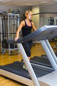 Молодая женщина в тренирующемся спортзале. ходьба на на машине — Стоковое фото