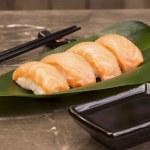 sushi syake på grönt blad med sojasås och pinnar — Stockfoto #54145809