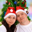 Young happy smiling couple near green decorated Christmas tree — Stock Photo #57757761