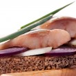 The pieces of salted herring on rye bread with slices of red onion — Stock Photo #64324017
