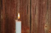 One burning candle at an old red wall — Stok fotoğraf