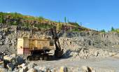 Excavator standing in quarry between stones and sand — Stock Photo