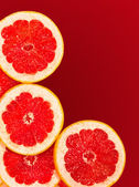 Fresh grapefruit slices isolated on a gradient red — Stock Photo