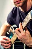 Man playing on the guitar, picture with a light toning — Stock Photo