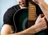 Guitarist holding an acoustic guitar — Стоковое фото