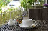 White coffee set on the table at an outdoor cafe on a summer day — Foto Stock