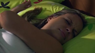 Young Woman In Bed Waking Up At Morning Snoozing Alarm Clock — Stock Video