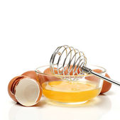 Wire whisk and brown eggs — Stock Photo