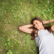 Young brunette woman enjoying the lying on her back on the green — Stock Photo #56468785