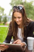 Young brunette woman using digital tablet outdoor in a park. Sum — Stock Photo