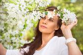 Porträtt av våren brunett tjej stå utomhus i blommande tr — Stockfoto