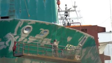 A ship worker repainting some green parts of the big ship GH4 — Stock Video