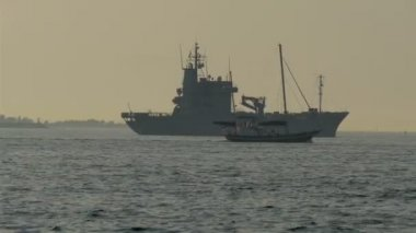Warship and a small viking boat crossing. — Stock Video
