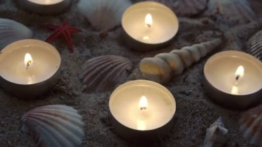 Six candles and some seashells on the sand — Stock Video