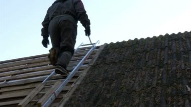 A roofer climbing on to the ladder — Stock Video