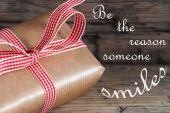 Gift With Red Ribbon Saying Be The Reason Someone Smiles — Photo