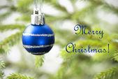 Blue Christmas Ball on Christmas Tree with Text Merry Christmas — Stock Photo