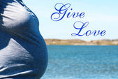 Pregnant Woman Infront Blue Sea With Text Give Love — Foto de Stock