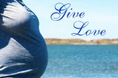 Pregnant Woman Infront Blue Sea With Text Give Love — Stockfoto