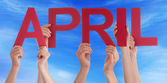 Many People Hands Holding Red Straight Word April Blue Sky — Stock Photo