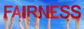 Hands Holding Red Straight Word Fairness Blue Sky — Stock Photo