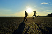 Brother and sister jumping on the beach — Foto Stock
