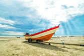Boat on the beach with ray of light — Stock Photo