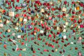 Plenty of colorful locks on bridge sign of eternal love devotion — 图库照片
