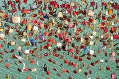 Plenty of colorful locks on bridge sign of eternal love devotion — Stock fotografie