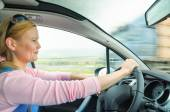 Attractive adult woman safe carefully driving car suburban road — Stock Photo
