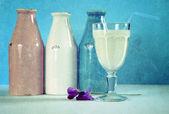 Vintage grunge style pink, white and blue milk bottles — Stock Photo