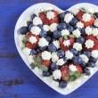 Red white and blue berries with fresh whipped cream stars. — Stock Photo #54776007