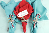 Merry Christmas table place setting red and aqua blue napkins — Stock Photo