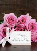 Mothers Day pink roses on rustic dark wood table. — Stock Photo