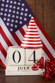 Fourth of July vintage wood calendar with flag background. — Stock Photo