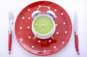 Mealtime table place setting with alarm clock — Photo