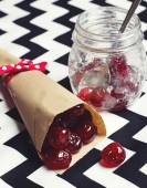 Glace cherries in paper cone on chevron background — Stock Photo
