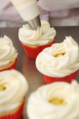 Whipped butter cream frosting applied to cupcakes — Stock Photo