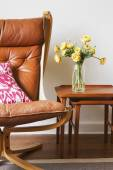 Cropped vintage tan leather chair with teak side tables — Stock Photo