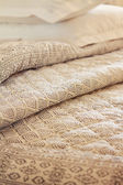 Close up of folds of luxury quilt and pillow in background — Stock Photo