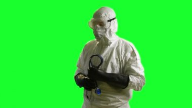 Ebola doctor in a hazmat suit looks at camera green screen — Stock Video