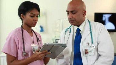 Tilt doctor and nurse going over chart — Stock Video