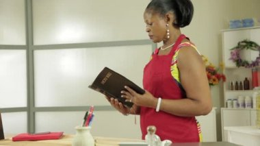 Woman small business owner reads her bible — Stock Video