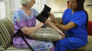 Tilt up to home healthcare nurse putting on blood pressure cuff — Stock Video