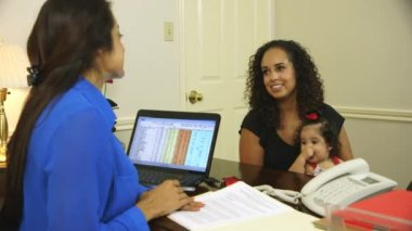 Hispanic mom with her baby talking to a business woman at her desk — Stock Video