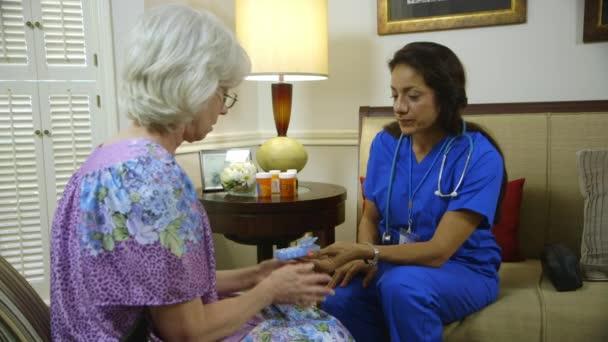 Enfermera profesional de la salud casera mostrando a su paciente anciano de la caja de la píldora — Vídeo de stock