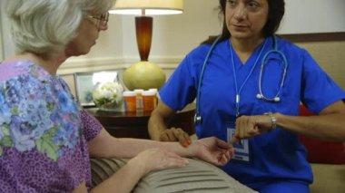 Domowej opieki zdrowotnej pielęgniarka kontroli impulsów jej pacjenta — Wideo stockowe