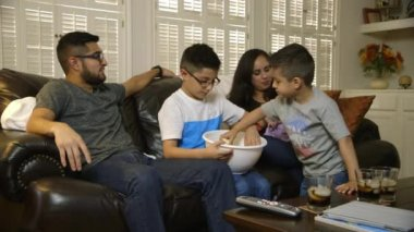 Young hispanic family eating popcorn and watching tv — Stock Video