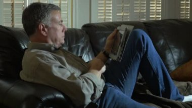 Man relaxing on his couch drinking coffee and using a tablet pc — Stock Video