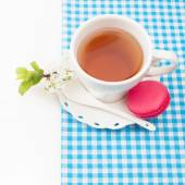 Cup of tea and sweet and colourful french macaroon and a cherry — Stock Photo